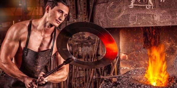Blacksmith forging a weight plate